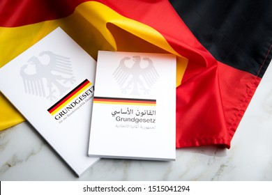 Hamburg, Hamburg/Germany – 09-23-2019: The constitution basic law book of Germany in German and Arabic language on flag and marble background
