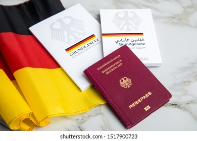 Hamburg, Hamburg/Germany – 09-23-2019: Passport and  constitution basic law book of Germany in German and Arabic language on flag and marble background