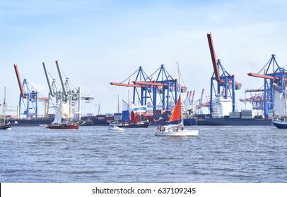 Hamburg harbor, birthday parade with various ships. View to Hamburg harbor with harbor cranes.
