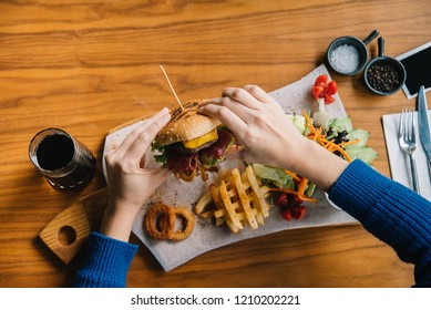 Hamburger anf fried potatoes eater human, soft drink, onion rings and salad
