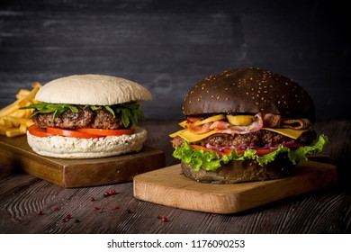 Hamburger with beef and bacon and a white hamburger with french fries on a wooden background.