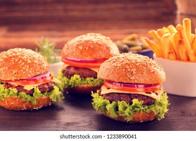 Hamburger with beef meat and fresh vegetables on wooden background, close up vintage view