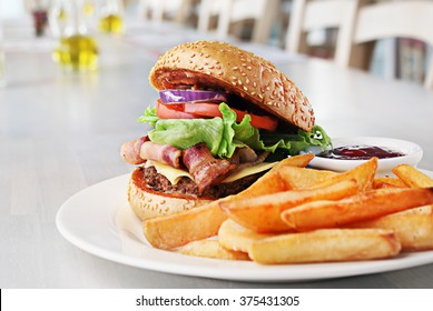 Hamburger with beef meet, vegetables, ketchup and chips on plate