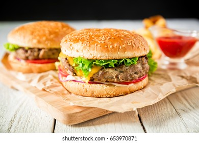 Hamburger with beef, sauce and french fries on wood table. American tasty food