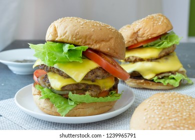 Hamburger with beef,cheese,lettuce,onion and tomato in white dish on concrete table.