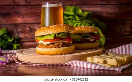 Hamburger and beer on wooden board