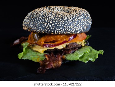 Hamburger with a black loaf and grilled bacon, on a dark background.
