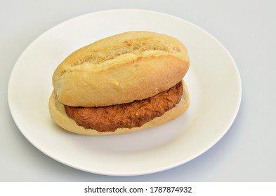 hamburger in bun on white plate, closeup, isolated on white background