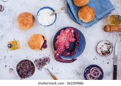 Hamburger buns with Cooked whole octopus sliced and yogurt sauce on stone rustic background, top view.