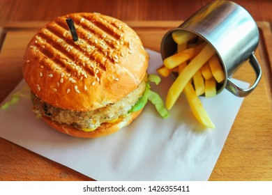 Hamburger with cheese and chop and a cup of deep fried potatoes