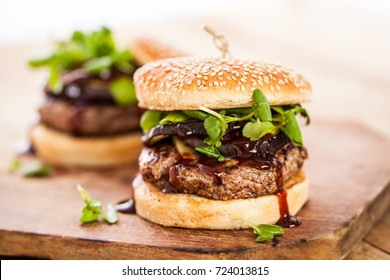 hamburger with cheese, grilled meat, eggplant, barbecue sauce and herbs on top