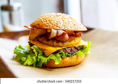 Hamburger with cheese, steak, onion rings, lettuce, pineapple and bacon.