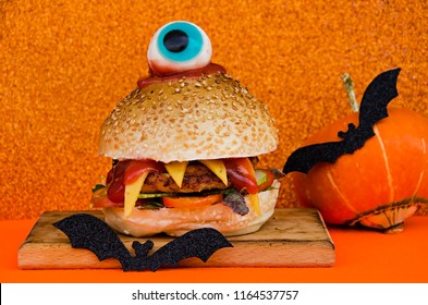 Hamburger with chicken cutlet, cheese, vegetables and sauce in the form of a monster with one eye. Cyclops. Menu on Halloween.