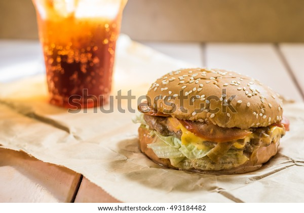 Hamburger with cola on table