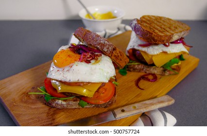 Hamburger with egg, cheese, onions, tomatoes and sliced brown bread
