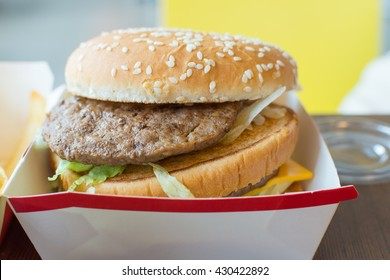 Hamburger is a fast food make from bun, meat, cheese and vegetable in white paper box in restaurant