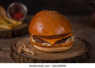 Hamburger with french fries, ketchup, mustard and fresh vegetables on a cutting wooden board.