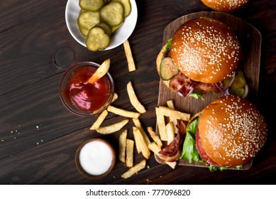Hamburger and french fries on wooden table, top view.