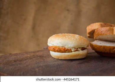 hamburger with fresh sliced bread on wooden background