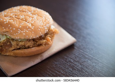 hamburger with fried chicken on wood background.