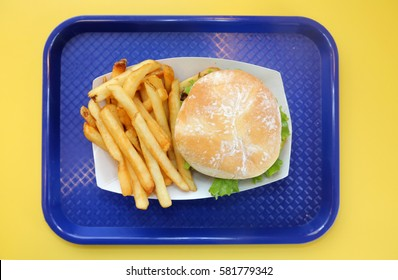 hamburger and fries. cheese bacon burger and French fries with lettuce, tomato and secret sauce on a blue plastic serving tray on a yellow Formica table.