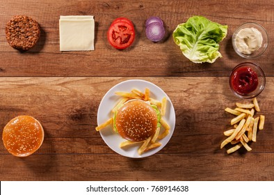 Hamburger ingredients on wooden table with an assembled burger in center on a plate - fast food background