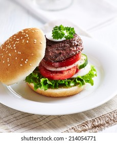Hamburger with lettuce, tomatoes, cucumber, white onion and fresh herbs. Concept for a tasty und hearty meal.