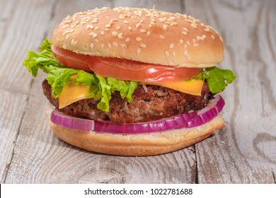 The hamburger lies on an old wooden table. On the table is a hamburger, tomato sauce, cherry tomatoes, a jar of spices.