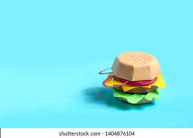 Hamburger made of paper. Volumetric handmade paper objects. Paper art and craft. Trendy hobby. Minimal artistic food concept. Copy space