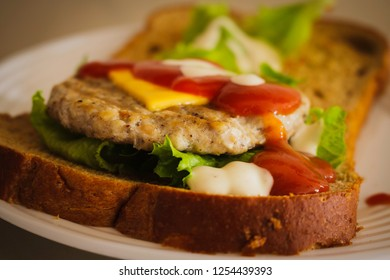 Hamburger made from whole wheat sliced bread, cheese, lettuce topped with tomato sauce on a white plate