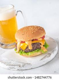 Hamburger with mug of beer on the wooden board