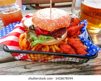 Hamburger with nuggets on twisted french fries, soft focus