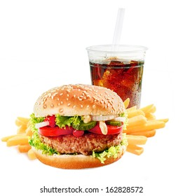 Hamburger on a asesame bun with iced soda drink and crisp golden potato French fries on a white background