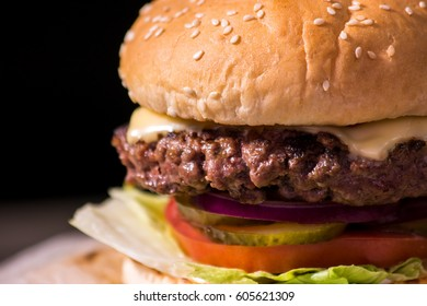 Hamburger on black background. Sesame bun and grilled meat.
