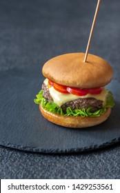 Hamburger on the black stone board close up