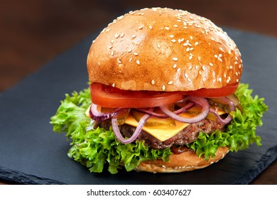 Hamburger on stone table with black background. Fastfood meal. Delicious Hamburger. Gourmet hamburger.