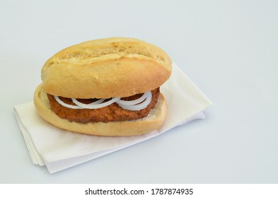 hamburger with onion rings in bun on white napkin, closeup, isolated on white background
