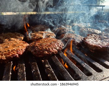 Hamburger patties on the BBQ grill with flames