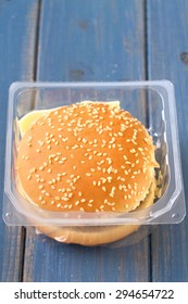hamburger in plastic box on blue wooden background