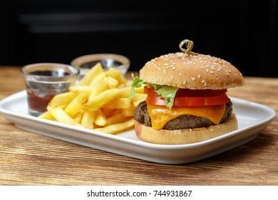 hamburger with potatoes and sauces on a plate in a restaurant