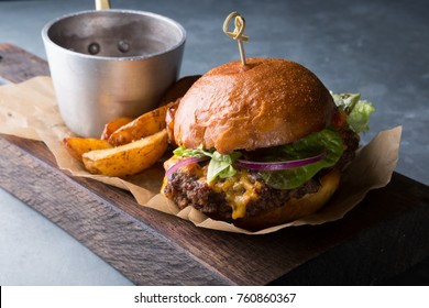 Hamburger with potatoes served on wooden chopping board