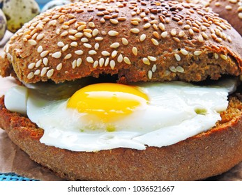Hamburger with quail eggs. Rye bun with sesame. Close up. Fresh hot bun with fried quail eggs.