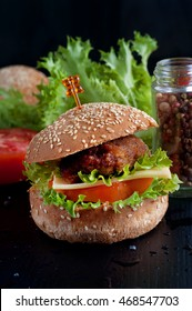 Hamburger with salad, cheese, tomato, meat on black backdrop. Popular snack.
