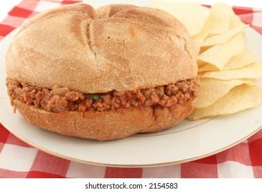 hamburger (sloppy joe) in sauce inside a bun and chips