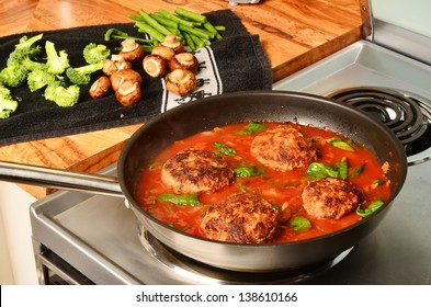 Hamburger steaks in tomato gravy simmering on hot electric stove with vegetables being prepared on wooden counter top.