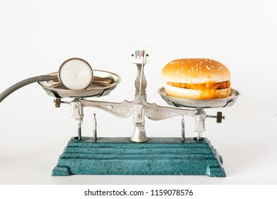 Hamburger and stethoscope in weight scale on white background.Unhealthy food and diet concept.