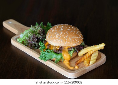 Hamburger with vegetables in wooden tray on dark wooden background / Select focus and space for texts