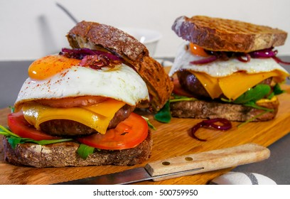 Hamburgers with egg, cheese, onion on sliced brown bread
