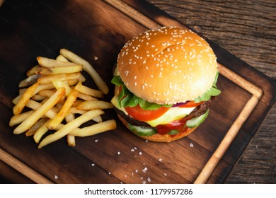 Hamburgers and French fries on the wooden cutting bord