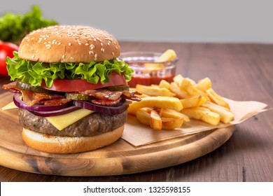 Hamburgers with fried bacon and sliced pickles  on a cutting board with french fries and tomato sauce
